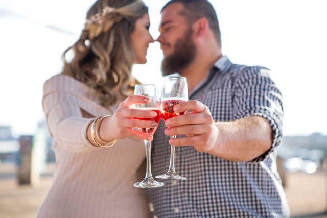 Woman and man holding clear wine glass